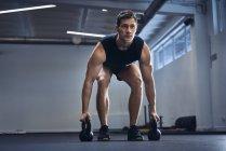 Мужчина делает гиревые упражнения в спортзале — стоковое фото