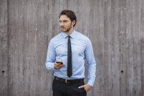 Empresário em pé na parede de concreto segurando smartphone — Fotografia de Stock