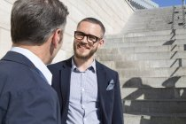 Two smiling businessmen talking at stairs outdoors — Stock Photo