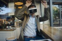 Зрелый бизнесмен сидит в кафе, просматривая vr очки, танцуя — стоковое фото