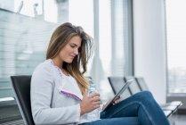Joven mujer de negocios sentada en la sala de espera usando tableta - foto de stock