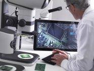 Engenheiro usando um microscópio estéreo 3d para controle de qualidade na fabricação de placas de circuito para a indústria eletrônica — Fotografia de Stock