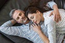 Couple détendu couché sur le canapé à la maison — Photo de stock