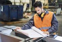 Hombre usando ropa de trabajo protectora mirando el plano en la fábrica - foto de stock