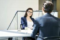 Бизнесмен и бизнесмен разговаривают за столом в современном офисе — стоковое фото