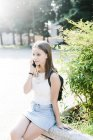 Young woman with backpack resting in a park talking on cell phone — Stock Photo