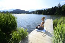 Германия, Миттенвальд, женщина, практикующая йогу на пристани у озера — стоковое фото