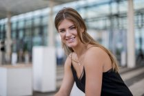 Портрет улыбающейся молодой женщины, сидящей на улице — стоковое фото