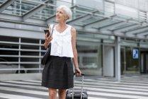 Усміхнена старша жінка з мобільного телефону і багажу на ходу в місті — стокове фото