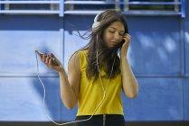 Портрет молодой женщины, слушающей музыку с наушниками и сотовым телефоном — стоковое фото