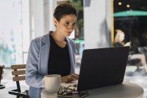 Молодая деловая женщина, сидящая в кафе и с ноутбуком — стоковое фото