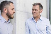 Два бизнесмена разговаривают у стены на открытом воздухе — стоковое фото