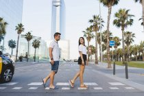 Young couple crossing street in city and flirting — Foto stock