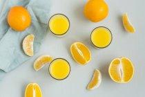 Verres de jus d'orange fraîchement pressé et tranches d'orange — Photo de stock