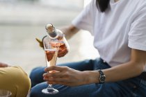 Gros plan de la femme versant du vin mousseux rougissant — Photo de stock