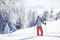 Austria, Tyrol, smiling snowshoe hiker standing in snow — Stock Photo
