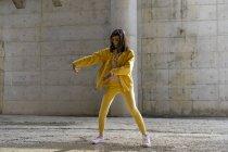Donna che indossa vestiti di jeans gialli, danza — Foto stock