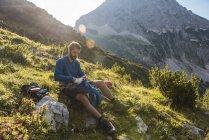 Austria, Tirolo, Escursionista seduto su una roccia in montagna — Foto stock