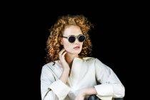 Ritratto di giovane donna elegante con capelli rossi ricci che indossa occhiali da sole davanti allo sfondo nero — Foto stock