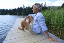 Germany, Mittenwald, mature man relaxing on jetty at lake — стоковое фото