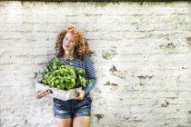 Ritratto di giovane donna con erbe fresche in scatola di legno appoggiata al muro di mattoni bianchi — Foto stock