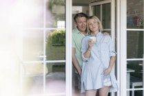 Smiling mature couple standing at French window — Stock Photo