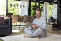 Mature man sitting on carpet at home using a tablet — Stock Photo