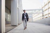 Uomo d'affari sorridente con borsa a tracolla in città in movimento — Foto stock