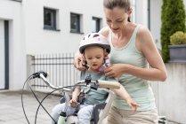 Мать и дочь, дочь в шлеме, сидят в детском кресле — стоковое фото