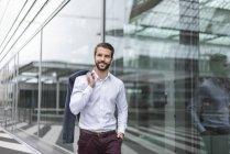 Portrait de jeune homme d'affaires souriant à la façade de verre — Photo de stock