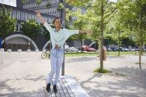 Jovem feliz balanceando no banco — Fotografia de Stock