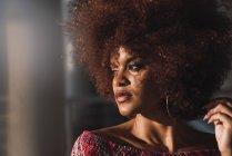 Портрет чуттєвої жінки з фарбованими локони на розмитий фон — стокове фото