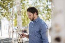 Empresário usando smartphone ao ar livre na natureza — Fotografia de Stock
