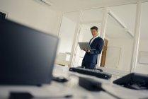 Uomo d'affari in piedi in ufficio, utilizzando il computer portatile — Foto stock