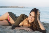 Beautiful woman relaxing on the beach at sunset, portrait — Stock Photo