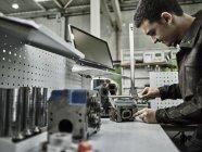 Рабочий на металлообрабатывающем заводе, измеряющий головку цилиндра с помощью суппорта — стоковое фото