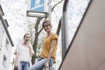 Freundinnen amüsieren sich in der Stadt, rutschen auf Geländer der Unterführung — Stockfoto
