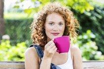 Портрет рыжеволосой девушки с розовой чашкой кофе на открытом воздухе — стоковое фото