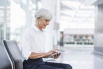 Senior businesswoman sitting in waiting area and using tablet — Stock Photo