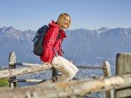 Austria, Tirolo, Escursione donna seduta sulla recinzione, prendendo una pausa — Foto stock