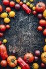 Diferentes tipos de tomates sobre fondo de madera, espacio de copia - foto de stock