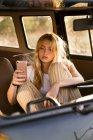 Jeune femme s'asseyant dans une fourgonnette utilisant le téléphone portable — Photo de stock