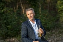 Portrait of businessman with beverage in nature — Stock Photo