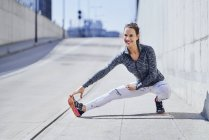 Femme coureuse étirant les jambes pendant l'entraînement urbain — Photo de stock