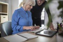 Zwei hochrangige Kollegen arbeiten gemeinsam am Schreibtisch im Büro — Stockfoto