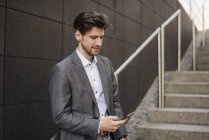 Uomo d'affari che utilizza il telefono cellulare sulle scale — Foto stock