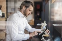 Businessman using tablet in a cafe — Stock Photo