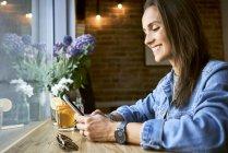 Усміхнена молода жінка з тарілкою млинців з використанням телефону в кафе — стокове фото