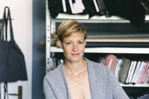 Mulher branca designer de moda no estúdio olhando para a câmera com sorriso — Fotografia de Stock