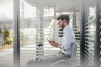 Homme d'affaires assis sur la plate-forme de la station en utilisant un téléphone portable — Photo de stock